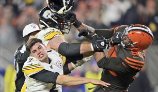 Cleveland Browns defensive end Myles Garrett (95) hits Pittsburgh Steelers quarterback Mason Rudolph (2) with a helmet during the second half of an NFL football game Thursday, Nov. 14, 2019, in Cleveland. (AP Photo/David Richard)