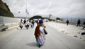 Pedestrians walk alongside a highway that has been  blocked by supporters of former President Evo Morales, in El Alto, Bolivia, Thursday, Nov. 14, 2019.   In self-exile in Mexico after resigning under pressure from the armed forces, Morales says he would be willing to return to Bolivia, and his supporters are making a show of force in the streets while his party controls a majority in both houses of Congress. (AP Photo/Natacha Pisarenko)