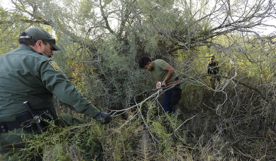 In this Wednesday, Nov. 6, 2019, photo, Border Patrol agents apprehend a man thought to have entered the country illegally, near McAllen, Texas, along the U.S.-Mexico border. (AP Photo/Eric Gay) **FILE**