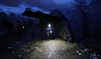 In this photo taken Wednesday, Nov. 13, 2019, a migrant walks in the Vucjak refugee camp outside Bihac, northwestern Bosnia. The European Union's top migration official is warning Bosnian authorities of a likely humanitarian crisis this winter due to appalling conditions in overcrowded migrant camps in the country. (AP Photo/Darko Vojinovic)