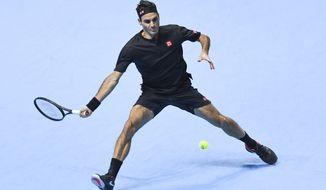 Roger Federer of Switzerland returns to Novak Djokovic of Serbia during their ATP World Tour Finals singles tennis match at the O2 Arena in London, Thursday, Nov. 14, 2019. (AP Photo/Alberto Pezzali)
