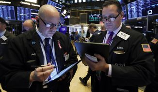 FILE - In this Nov. 7, 2019, file photo traders Jeffrey Vazquez, left, and Edward Curran work on the floor of the New York Stock Exchange. The U.S. stock market opens at 9:30 a.m. EST on Thursday, Nov 14. (AP Photo/Richard Drew, File)