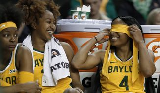 Baylor's DiDi Richards, left, smiles as she and Te'a Cooper (4) joke on the bench late in the second half of the team's NCAA college basketball game against Houston Baptist in Waco, Texas, Thursday, Nov. 14, 2019. (AP Photo/Tony Gutierrez)
