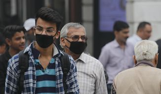 Indian walk wearing masks to protect against pollution in New Delhi, India, Thursday, Nov. 14, 2019. Schools in India's capital have been shut for Thursday and Friday after air quality plunged to a severe category for the third consecutive day, enveloping New Delhi in a thick gray haze of noxious air. (AP Photo/Manish Swarup)