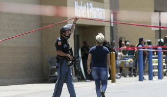 In this Aug. 3, 2019, file photo, an employee crosses into the crime scene following a shooting at a Walmart in El Paso, Texas. Walmart has quietly hired off-duty officers at dozens of its stores across El Paso, where a gunman opened fire in August at one of the retail giant's locations and killed 22 people. The move comes as Walmart plans Thursday, Nov. 14, to reopen the store where the attack happened amid ongoing lawsuits over safety. (Mark Lambie/The El Paso Times via AP, File)