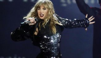 """FILE - This May 8, 2018 file photo shows Taylor Swift performing during her """"Reputation Stadium Tour"""" opener in Glendale, Ariz. Swift says she may not be performing at the American Music Awards because the men who own her old recordings won't allow her to play her songs.  Swift said on Instagram Thursday that she planned to play a medley of her hits when she's named Artist of the Decade at the American Music Awards on Nov. 24. But Swift says the men who own the music, Scooter Braun and Scott Borchetta, are calling the performance an illegal re-recording.  (Photo by Rick Scuteri/Invision/AP, File)"""