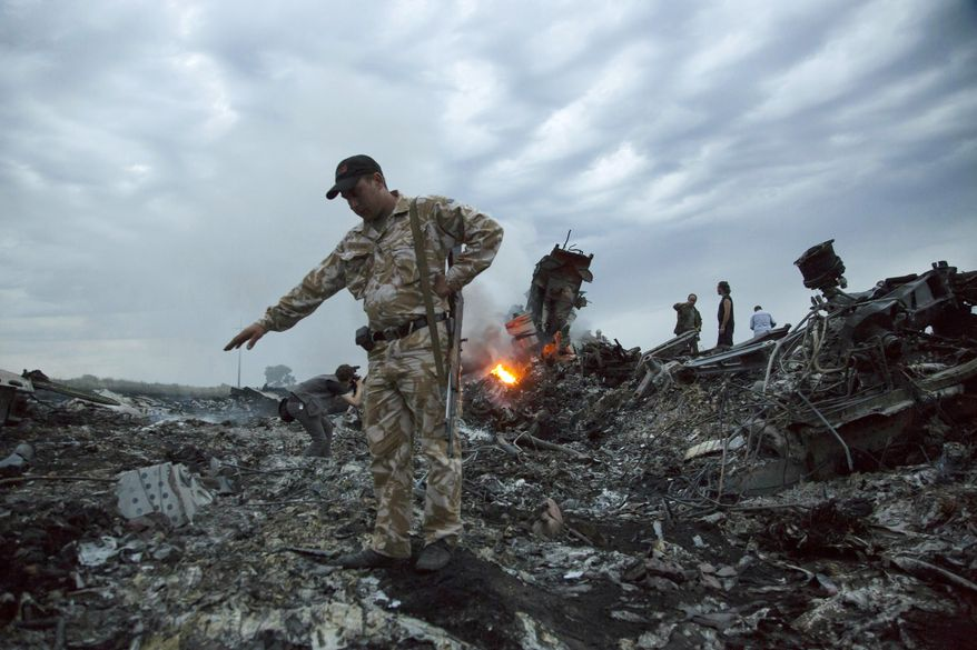 In this July 17, 2014, file photo, people walk amongst the debris at the crash site of MH17 passenger plane near the village of Grabovo, Ukraine, that left 298 people killed. An international team of investigators piecing together a criminal case in the July 2014 shooting down Malaysia Airlines Flight 17 over eastern Ukraine said Thursday, Nov. 14, 2019, that evidence suggests links between Russia and rebels in the region were closer than previously believed. (AP Photo/Dmitry Lovetsky, File)