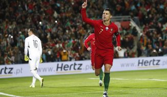 Portugal's Cristiano Ronaldo celebrates after scoring the opening goal during the Euro 2020 group B qualifying soccer match between Portugal and Lithuania at the Algarve stadium outside Faro, Portugal, Thursday, Nov. 14, 2019. (AP Photo/Armando Franca)