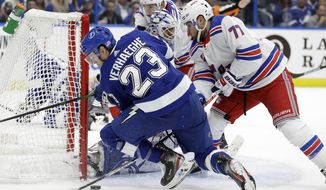 Tampa Bay Lightning center Carter Verhaeghe (23) gets knocked down by New York Rangers defenseman Tony DeAngelo (77) during the second period of an NHL hockey game Thursday, Nov. 14, 2019, in Tampa, Fla. (AP Photo/Chris O'Meara)