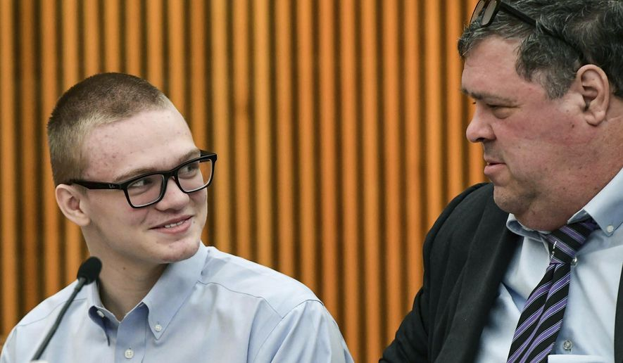 Jesse Osborne smiles while talking with attorney Frank Eppes during a break in the courtroom after testimony from his grandfather Tommy Osborne at a sentencing hearing at the Anderson County Courthouse Thursday, Nov. 14, 2019, in Anderson, S.C. The teen, who killed a first-grader on the playground of a South Carolina school and his father, faces 30 years to life without parole. (Ken Ruinard/The Independent-Mail via AP)
