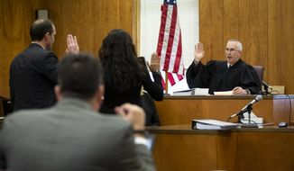 Judge Joel Yates swears in interpreters for Cristhian Bahena Rivera during an evidence suppression hearing at the Poweshiek County Courthouse on Wednesday, Nov. 13, 2019, in Montezuma, Iowa. Lawyers for Rivera, charged with killing University of Iowa student Mollie Tibbetts, asked a judge to throw out evidence discovered during a faulty interrogation, including the victim's body. (Brian Powers/The Des Moines Register via AP)