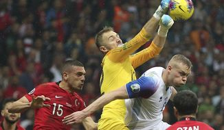 Turkey's goalkeeper Mert Gunok, center, hits the ball by his teammate Merih Demiral, left, and Iceland's Kolbeinn Sigthorsson, right, during the Euro 2020 Group H qualifying soccer match between Turkey and Iceland in Istanbul, Thursday, Nov. 14, 2019. (AP Photo)