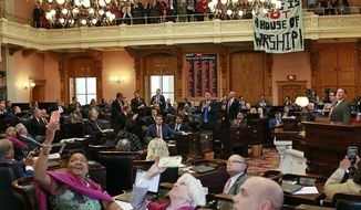 "In this April 10, 2019, file photo, some members of the Ohio House applaud following their vote while others photograph protesters who unfurled banners reading ""This is not a House of Worship"" and ""This is not a Doctor's office"" following a vote on the Heartbeat Bill at the Ohio Statehouse in Columbus, Ohio. (Brooke LaValley/The Columbus Dispatch via AP, File) ** FILE **"