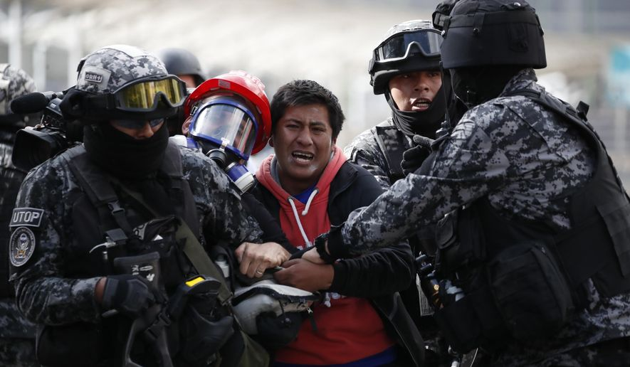 A supporter of former President Evo Morales is detained during clashes with police, in La Paz, Bolivia, Friday, Nov. 15, 2019. Bolivia's new interim president Jeanine Anez faces the challenge of stabilizing the nation and organizing national elections within three months at a time of political disputes that pushed Morales to fly off to self-exile in Mexico after 14 years in power. (AP Photo/Natacha Pisarenko)