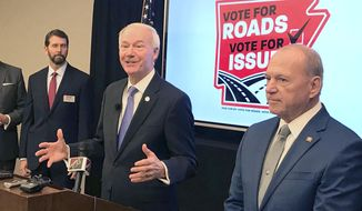 Arkansas Gov. Asa Hutchinson, center, speaks at a news conference at the Poultry Federation in Little Rock, Ark., Friday, Nov.  15, 2019 about the campaign to extend a half-cent sales tax for highways. Hutchinson called the effort to keep the tax his top priority among next year's ballot initiatives. The half-cent tax approved by voters in 2012 is to expire in 2023 unless voters extend it by approving a ballot measure that is part of a highway funding package passed by the Legislature earlier this year. (AP Photo/Andrew DeMillo)