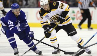 Boston Bruins right wing David Pastrnak (88) carries the puck under pressure from Toronto Maple Leafs center Nicholas Shore (26) during the first period of an NHL hockey game Friday, Nov. 15, 2019, in Toronto. (Frank Gunn/The Canadian Press via AP)