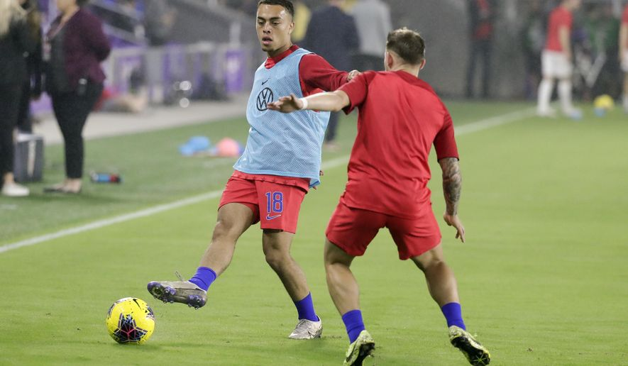 U.S. defender Sergino Dest warms up with teammates before a CONCACAF Nations League soccer match against Canada Friday, Nov. 15, 2019, in Orlando, Fla. (AP Photo/John Raoux)