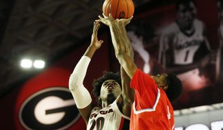 Georgia's Rayshaun Hammonds (20) takes a shot while being defended by Delaware State's Omari Peek-Green (2) during an NCAA college basketball game Friday, Nov. 15, 2019, in Athens, Ga. (Joshua L. Jones/Athens Banner-Herald via AP)