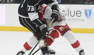 Los Angeles Kings right wing Tyler Toffoli (73), and Detroit Red Wings defenseman Mike Green vie for the puck during the second period of an NHL hockey game Thursday, Nov. 14, 2019, in Los Angeles. (AP Photo/Michael Owen Baker)