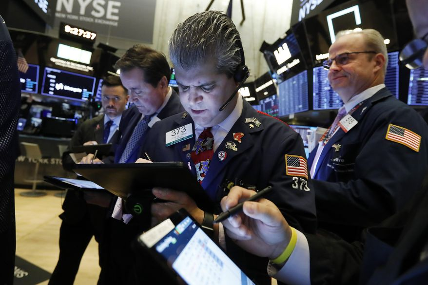 FILE - In this Nov. 7, 2019, file photo John Panin, center, works with fellow traders on the floor of the New York Stock Exchange. The U.S. stock market opens at 9:30 a.m. EST on Friday, Nov 15. (AP Photo/Richard Drew, File)