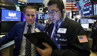 Specialist Stephen Naughton, left, and trader Michael Capolino work on the floor of the New York Stock Exchange, Friday, Nov. 15, 2019. Stocks are opening broadly higher on Wall Street as hopes continued to grow that the U.S. and China were moving closer to a deal on trade. (AP Photo/Richard Drew)