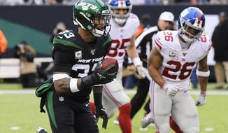 New York Jets strong safety Jamal Adams (33) runs past New York Giants' Saquon Barkley (26) for a touchdown during the second half of an NFL football game Sunday, Nov. 10, 2019, in East Rutherford, N.J. (AP Photo/Bill Kostroun)