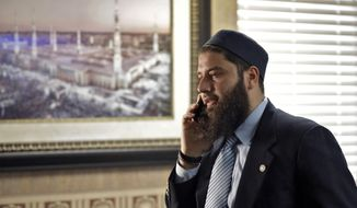 FILE - In this Feb. 20, 2019, file photo, Hassan Shibly, attorney for Hoda Muthana, the Alabama woman who left home to join the Islamic State group in Syria, speaks on a phone before a news conference in Tampa, Fla. A federal judge has ruled the U.S. government was correct when it determined Muthana, who joined the Islamic State, was not an American citizen despite her birth in the country. A family lawyer said Friday, Nov. 15, that they plan to appeal the ruling.  (AP Photo/Chris O'Meara, file)