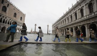 People use trestle bridges to walk in a flooded St. Mark's Square at Venice, Friday, Nov. 15, 2019.The high-water mark hit 187 centimeters (74 inches) late Tuesday, Nov. 12, 2019, meaning more than 85% of the city was flooded. The highest level ever recorded was 194 centimeters (76 inches) during infamous flooding in 1966. (AP Photo/Luca Bruno)