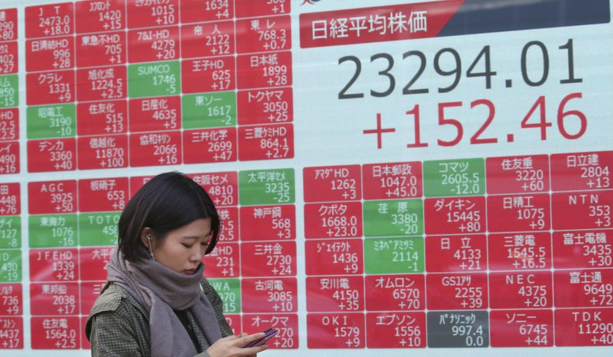 A woman walks by an electronic stock board of a securities firm in Tokyo, Friday, Nov. 15, 2019. Shares are higher in Asia after U.S. officials said China and the U.S. were getting close to an agreement to cool tensions over trade.(AP Photo/Koji Sasahara)