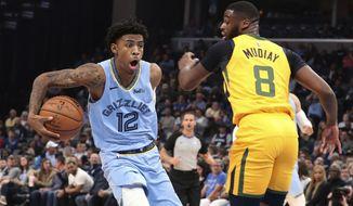 Memphis Grizzlies' Ja Morant (12) drives the ball around Utah Jazz's Emmanuel Mudiay (8)) during the first half of an NBA basketball game Friday, Nov. 15, 2019, in Memphis, Tenn. (AP Photo/Karen Pulfer Focht)