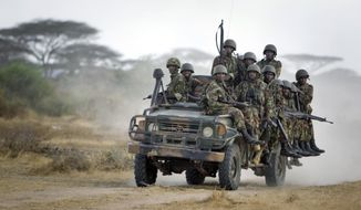 FILE - In this Monday, Feb. 20, 2012 file photo, Kenyan army soldiers ride on a vehicle at their base in Tabda, inside Somalia. A United Nations report published in Nov. 2019 says it has corroborated evidence of five attacks allegedly carried out by Kenya's military on communication masts belonging to neighboring Somalia's largest telecom provider Hormuud Telecom Somalia. (AP Photo/Ben Curtis, File)