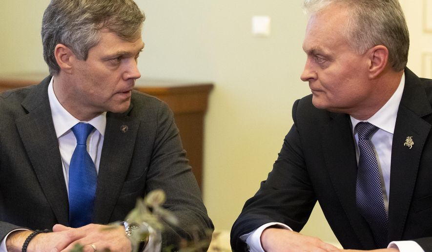 Lithuania's President Gitanas Nauseda, right, speaks to the Director of the State Security Department Darius Jauniskis prior to their meeting at the Presidential palace in Vilnius, Lithuania, Friday, Nov. 15, 2019. Lithuania's president has pardoned two Russians convicted of spying, his office said Friday, a move seen as a step toward a spy swap with neighboring Russia that could include a Norwegian citizen serving a 14-year sentence for espionage. (AP Photo/Mindaugas Kulbis)