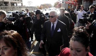Roger Stone, center, is swarmed by reporters while leaving federal court in Washington, Friday, Nov. 15, 2019. Stone, a longtime friend of President Donald Trump, has been found guilty at his trial in federal court in Washington. (AP Photo/Julio Cortez)