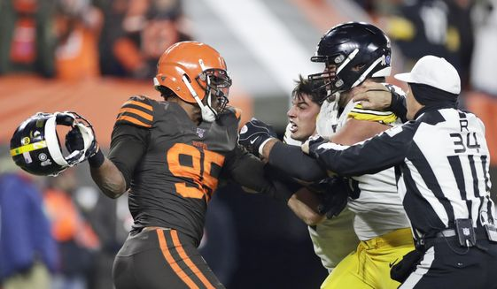 Cleveland Browns defensive end Myles Garrett, left, gets ready to hit Pittsburgh Steelers quarterback Mason Rudolph, second from left, with a helmet during the second half of an NFL football game Thursday, Nov. 14, 2019, in Cleveland. The Browns won 21-7. (AP Photo/Ron Schwane) ** FILE **