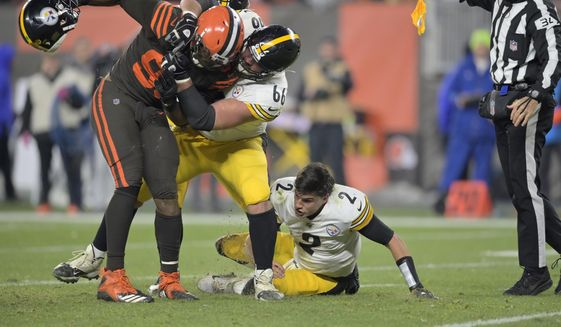 Cleveland Browns defensive end Myles Garrett, left, is grabbed by Pittsburgh Steelers offensive guard David DeCastro (66) after Garrett pulled the helmet off Pittsburgh Steelers quarterback Mason Rudolph (2) in the fourth quarter of an NFL football game, Thursday, Nov. 14, 2019, in Cleveland. The Browns won 21-7. (AP Photo/David Richard) ** FILE **