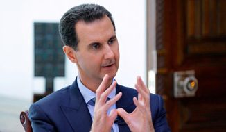 "In this photo released by the Syrian official news agency SANA, Syrian President Bashar Assad speaks during an interview with Russia24 TV and Rossiya Segodnya news agency, in Damascus, Syria, Friday, Nov. 15, 2019. Assad said the American presence in Syria will lead to armed ""resistance"" that will eventually force the U.S. troops to leave. (SANA via AP)"