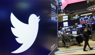 In this Feb. 8, 2018, file photo, the logo for Twitter is displayed above a trading post on the floor of the New York Stock Exchange.  In a policy published Friday, Nov. 15, 2019, Twitter said it is banning ads that contain references to political content, including appeals for votes, solicitations of financial support and advocacy for or against political content. The ban also includes any ads by candidates, political parties, elected or appointed government officials. (AP Photo/Richard Drew, File)