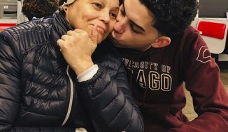 This photo provided by Cristian Padilla Romero, Tania Romero, left, is kissed by her son, Cristian Padilla Romero, in an Atlanta restaurant in 2019. The Yale University graduate student is trying to prevent the deportation of his mother to Honduras, a country where he says she won't get the medical treatment she needs as a survivor of stage-four cancer. (Cristian Padilla Romero via AP)