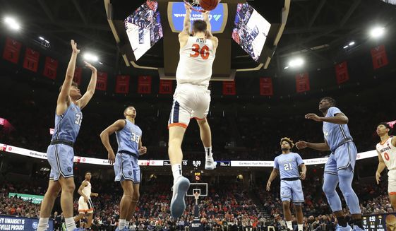 Virginia forward Jay Huff (30), surrounded by Columbia defenders, dunks the ball during an NCAA college basketball game in Charlottesville, Va., Saturday, Nov. 16, 2019. Virginia won 60-42. (AP Photo/Andrew Shurtleff) ** FILE **