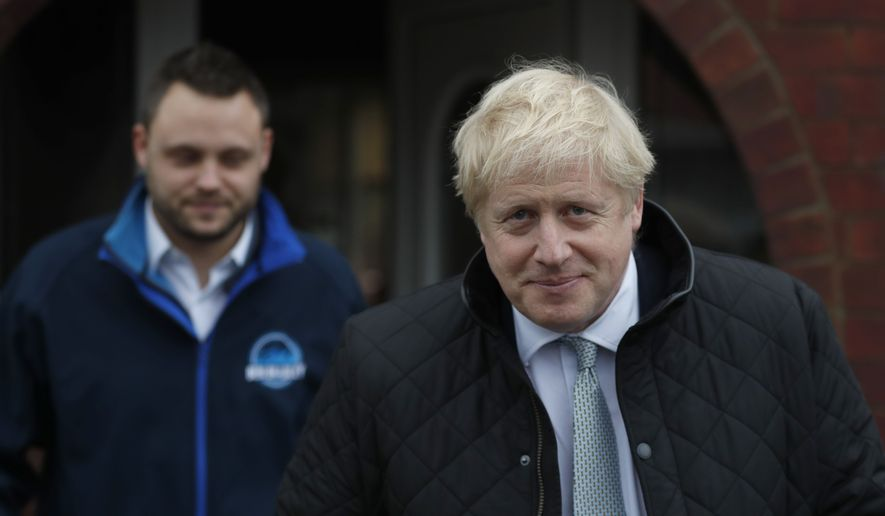 Britain's Prime Minister Boris Johnson, right with the Conservative party candidate for the Mansfield constituency canvasing during a General Election campaign trail stop in Mansfield, England, Saturday, Nov. 16, 2019.Britain goes to the polls on Dec.12. (AP Photo/Frank Augstein, Pool)