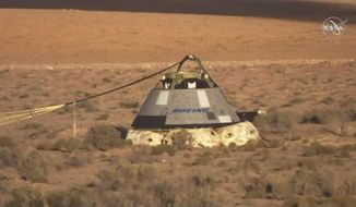 In this image made from a video provided by NASA the Starliner capsule rests on the ground after a test of Boeing's crew capsule launch abort system in White Sands Missile Range in N.M., on Monday, Nov. 4, 2019. Cochise County Arizona officials are hearing about possible emergency responses and road closures that might be required if the new reusable space capsule lands by parachute on a flat desert grassland (NASA via AP)