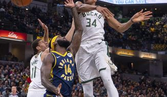Milwaukee Bucks forward Giannis Antetokounmpo (34) swats a shot by Indiana Pacers forward JaKarr Sampson (14) during an NBA basketball game, Saturday, Nov. 16, 2019, in Indianapolis. (AP Photo/Doug McSchooler)