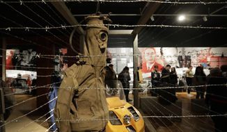 "In this picture taken on Tuesday, Nov. 12, 2019, visitors view the exhibition ""The Technology in Dictatorships,"" at the National technical Museum in Prague, Czech Republic. The exhibition, the first of that kind here, marks the 30th anniversary of the 1989 anti-communist Velvet Revolution by looking back at the surreal repression of a nation and resistance against it. (AP Photo/Petr David Josek)"