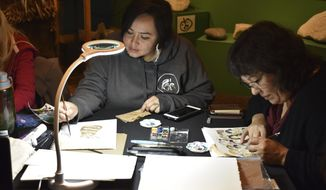 In this Thursday, Nov. 7, 2019 photo, artists Hanna Sholl and Cheryl Lacy work on illustrating the Pinguat Beads project and process through watercolor paintings in Kodiak, Alaska. Thirteen artists worked to replicate 147-year-old Alutiiq ceremonial garments as part of the Pinguat Beads project funded by the U.S. Bureau of Indian Affairs. The event on Nov. 7 was part of an intensive five-day workshop led by June Pardue, a master skin sewer and beader with family ties to the community of Old Harbor. (Sarah Lapidus/Kodiak Daily Mirror via AP)