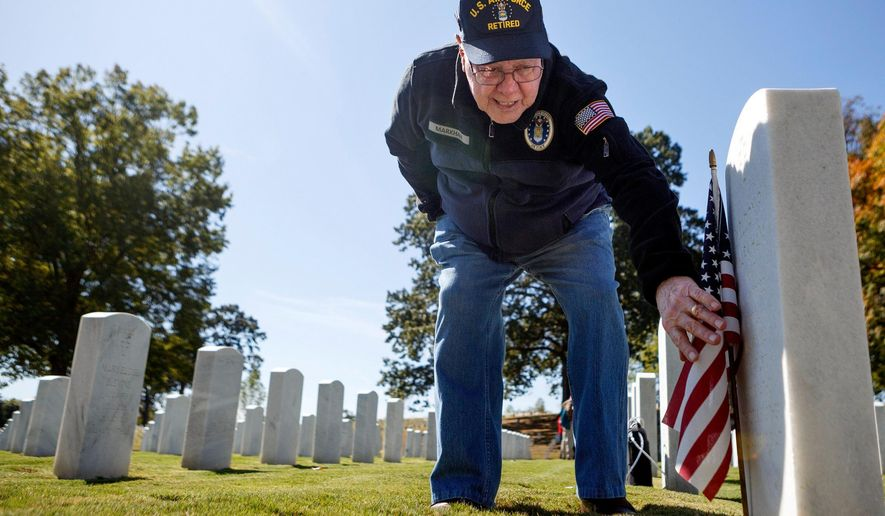 Wilbourne Markham reads his twin brother's headstone in the Chattanooga National Cemetery on Thursday, Oct. 17, 2019 in Chattanooga, Tenn. After his twin brother, Weldon, failed his physical, Wilbourne went back and took the physical in his place. They were both sworn in and served in the United States Air Force. (C.B. Schmelter/Chattanooga Times Free Press via AP)