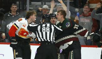 Linesman Tyson Baker (88) tries to break up Calgary Flames left wing Matthew Tkachuk, left, and Arizona Coyotes goaltender Darcy Kuemper (35) during a brawl during the second period of an NHL hockey game, Saturday, Nov. 16, 2019, in Glendale, Ariz. (AP Photo/Ross D. Franklin)