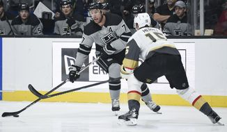 Los Angeles Kings center Jeff Carter, left, handles the puck while Vegas Golden Knights defenseman Jon Merrill defends during the second period of an NHL hockey game in Los Angeles, Saturday, Nov. 16, 2019. (AP Photo/Kelvin Kuo)