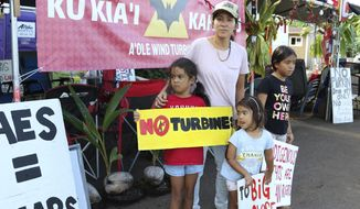 This Oct. 30, 2019, photo shows Sunny Unga, center, standing with her daughters, Joanne, from left, Alana and Ina while protesting the construction of eight wind turbines in Kahuku, Hawaii. The ongoing protest by mostly Native Hawaiians stalling construction of a $1.4-billion telescope on the Big Island has inspired protests on Oahu, the state's most populous island, with efforts to block the turbines and to stop the redevelopment of a beach park. (AP Photo/Jennifer Sinco Kelleher)