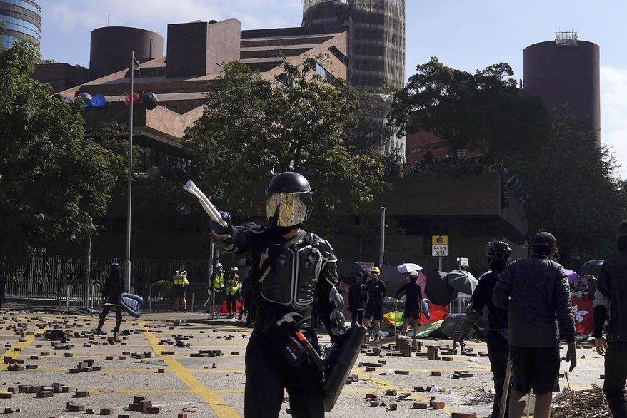 A protestor wearing a helmet and body armor gestures during unrest near Hong Kong Polytechnic University in Hong Kong, Sunday, Nov. 17, 2019. Police have fired tear gas at protesters holding out at Hong Kong Polytechnic University as overnight clashes resumed in the morning. (AP Photo/Vincent Yu)