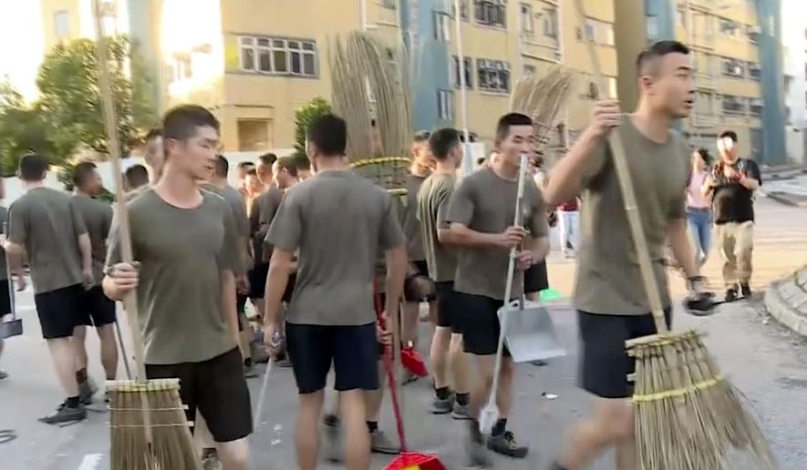 In this image made from video, People's Liberation Army soldiers, with brooms, arrive to clean up the protest area at Hong Kong Baptist University in Hong Kong, Saturday, Nov. 16, 2019. Troops from the Chinese army joined an effort to clean up debris outside the university, which was the site of clashes this week. (Television Broadcasts Limited Hong Kong via AP)